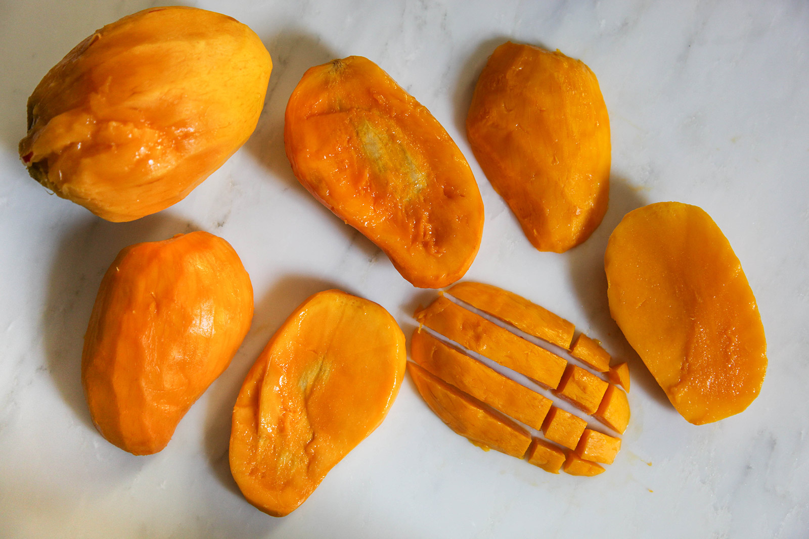 "Method of cutting sweet ripe mangoes for ""aamer pona"", simple dessert of Sweet Mango in Creamy Milk."