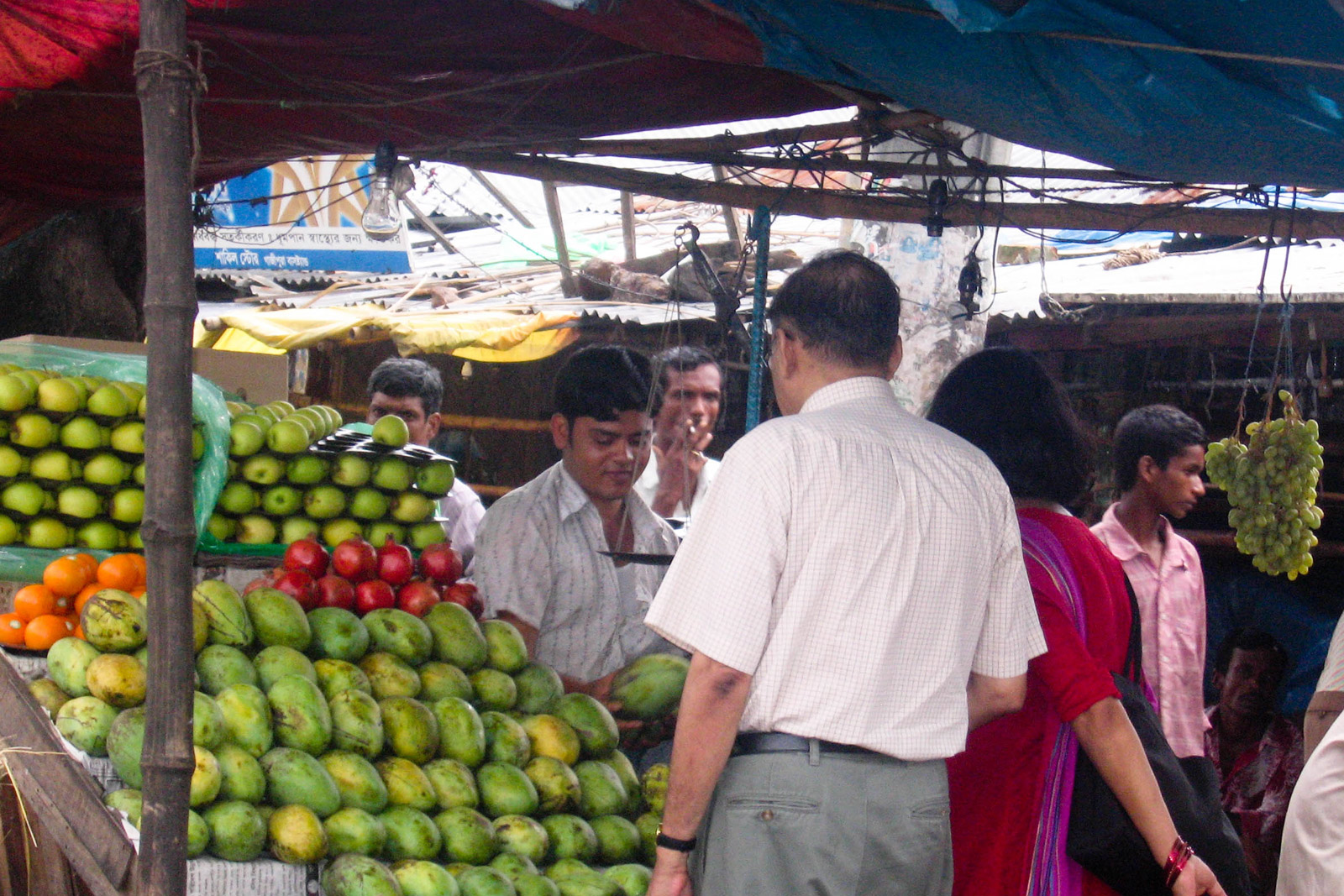 My dad and mom buying mangoes at an open-air market in Bangladesh.