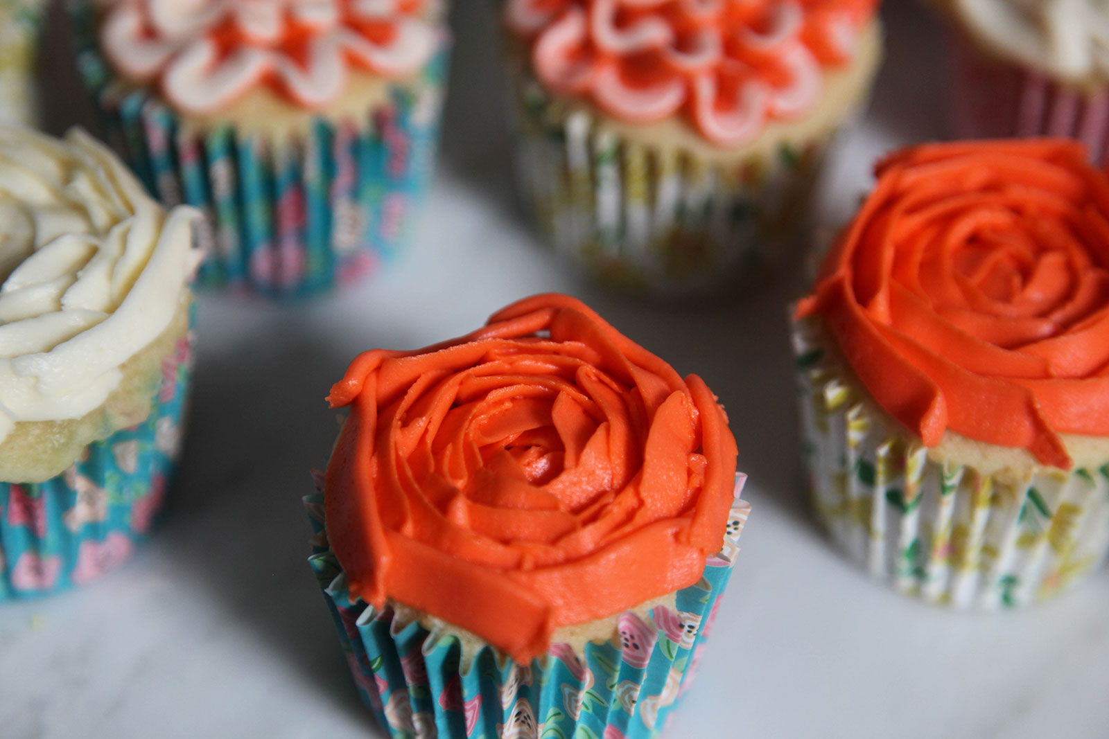 moist fluffy cupcakes with deep peach rosette decoration