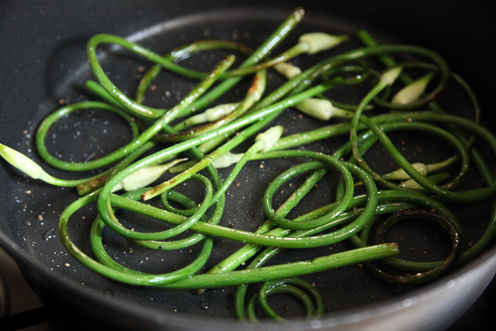 Sauteeing Garlic Scapes with Olive Oil, Sea Salt & Freshly Ground Pepper