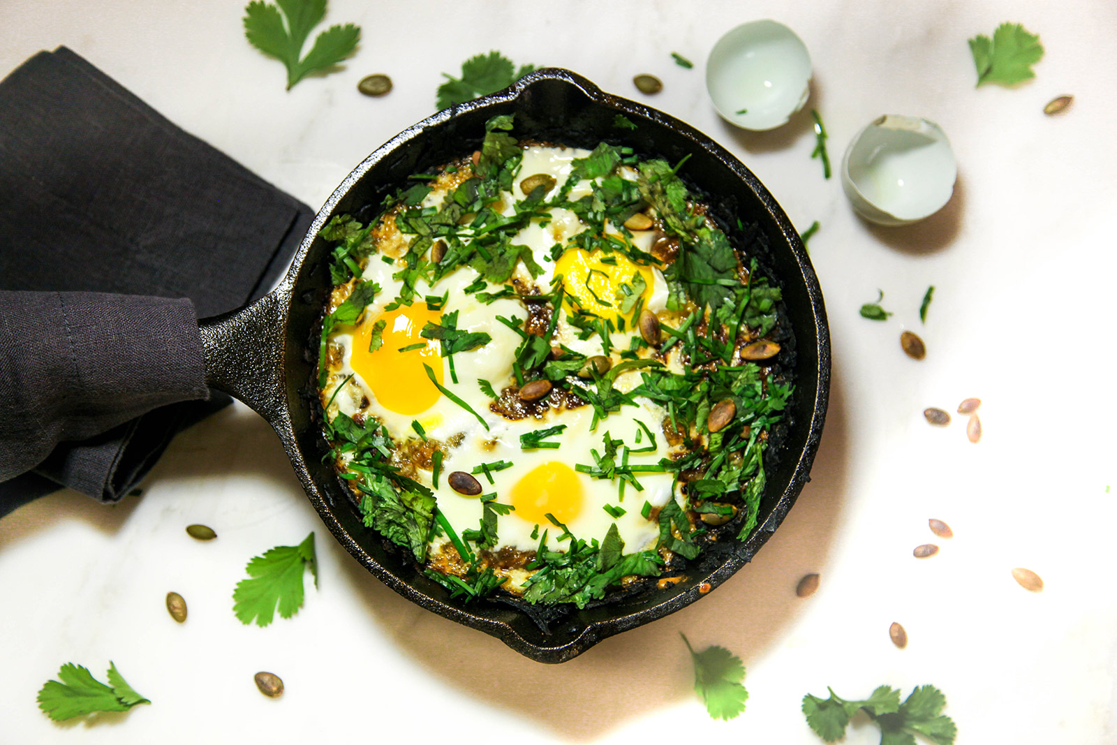 Crispy Potato Cake Nestled with Soft Baked Gooey Eggs, topped with Fresh Chives and Toasted Pumpkin Seeds